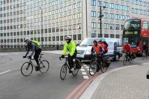 D56D49 Cyclists and traffic entering a roundabout in London, England.