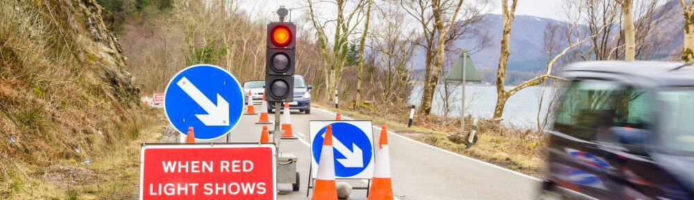 Traffic signs at the beginning of a roadworks area signalling the closure of a lane of a country road in Scotland.