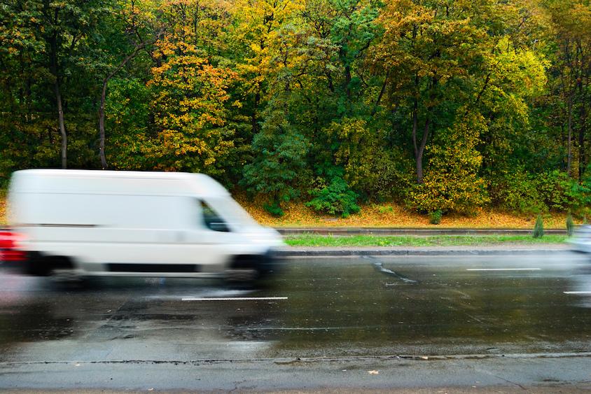 White van driving on wet road in autumn