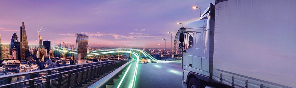 photo of a truck driving on a motorway with a large city in the background