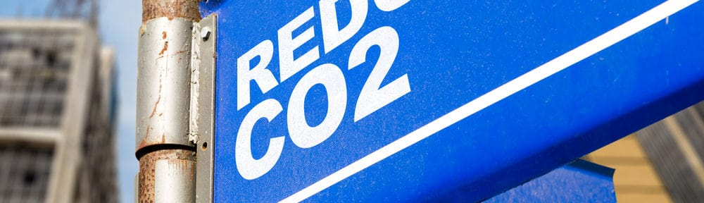 A blue sign with white writing saying Reduce co2
