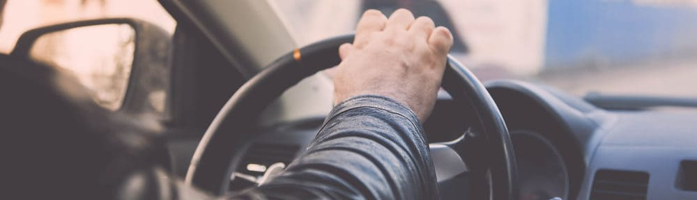 man driving a van is holding the steering wheel