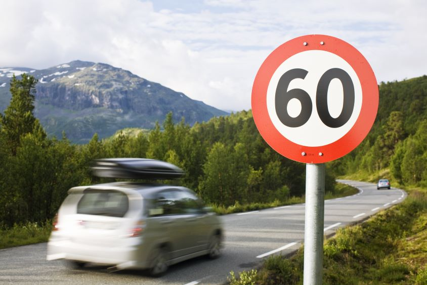 Car driving on country road past a 60mph speed limit sign