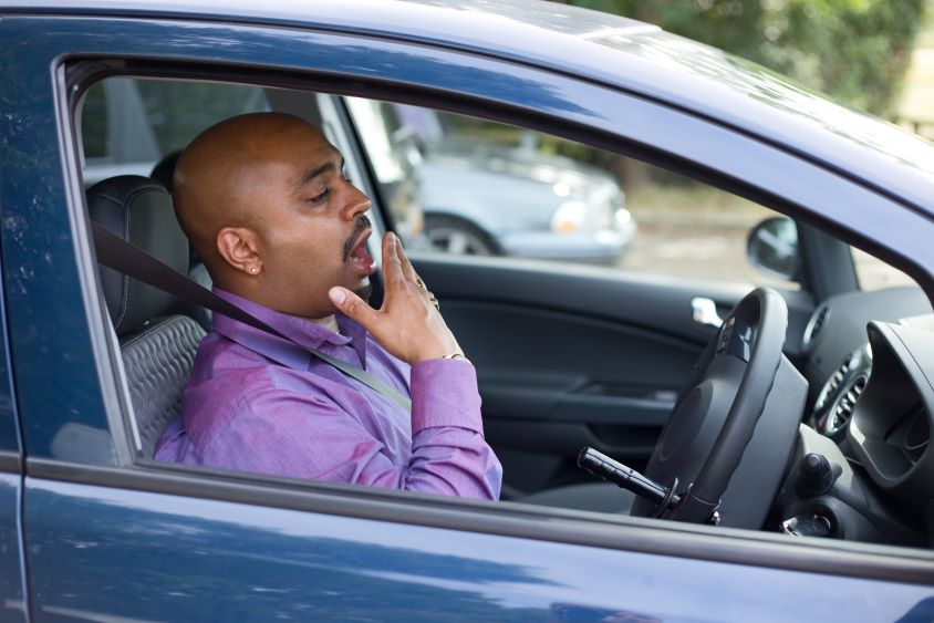 Male driver sat in car yawning