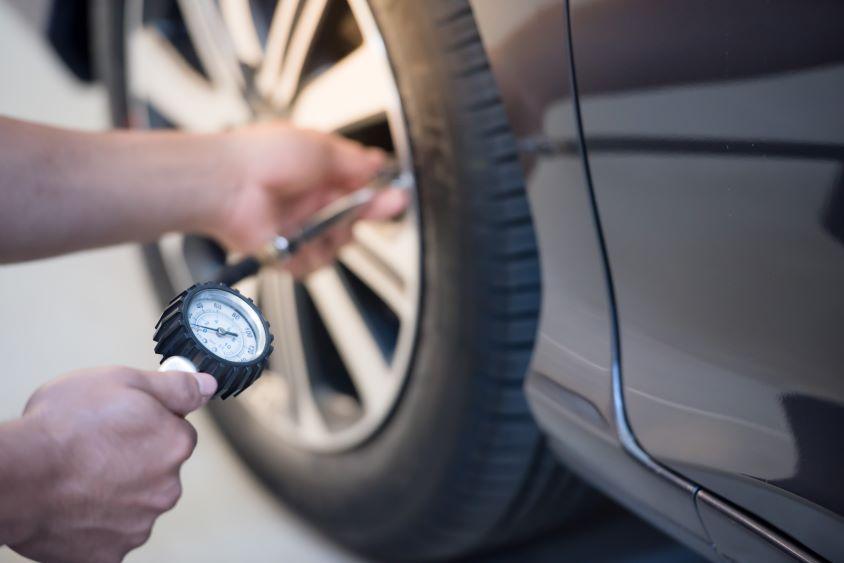 Pair of hands holding a pressure gauge, measuring car tyre pressure