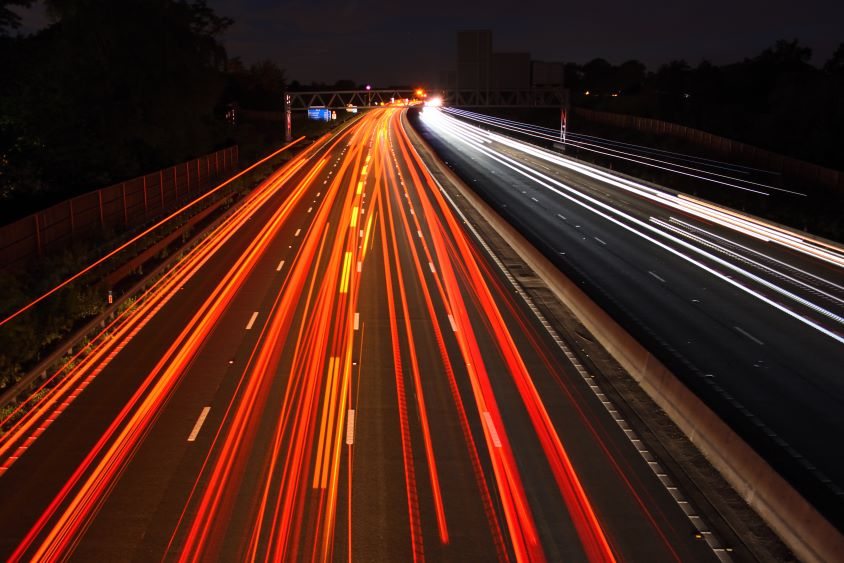 Aerial view of motorway at night with long exposure car headlights