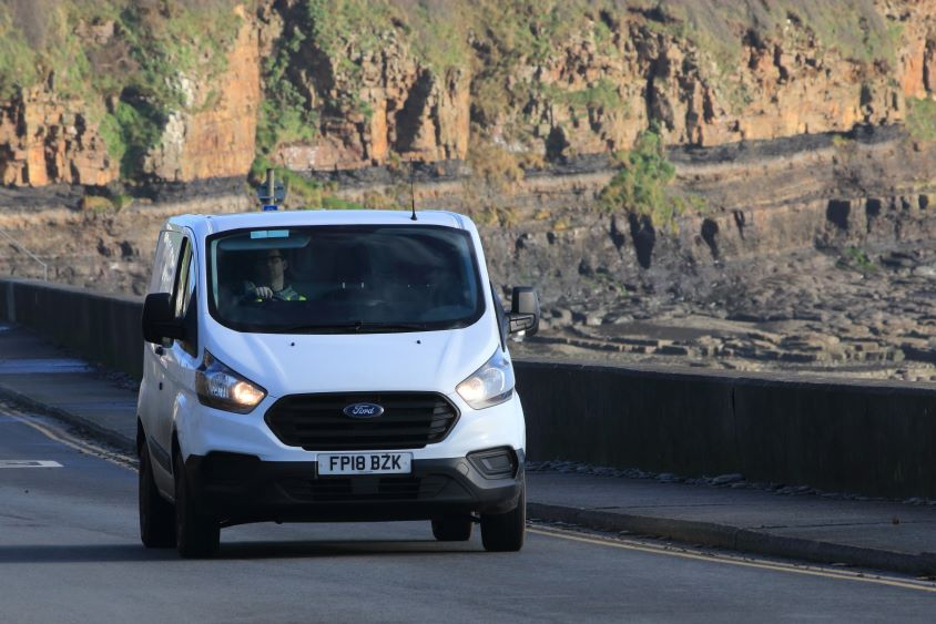White Ford van driving on road