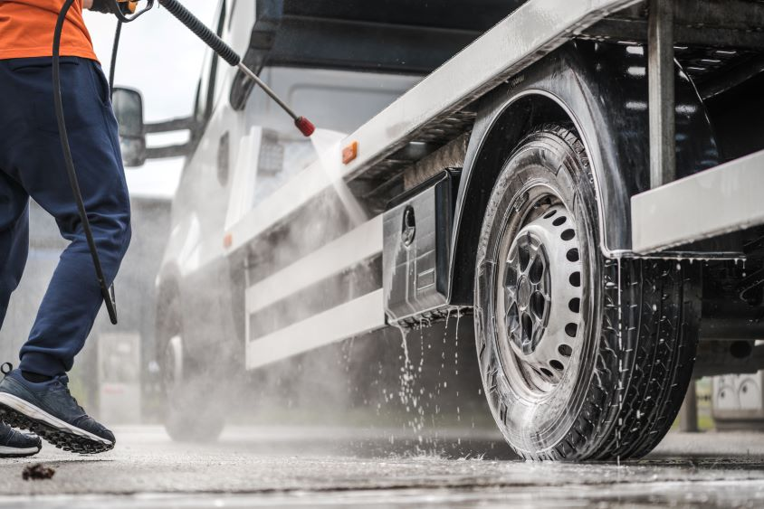 Person with a pressure washer spraying the side of a HGV