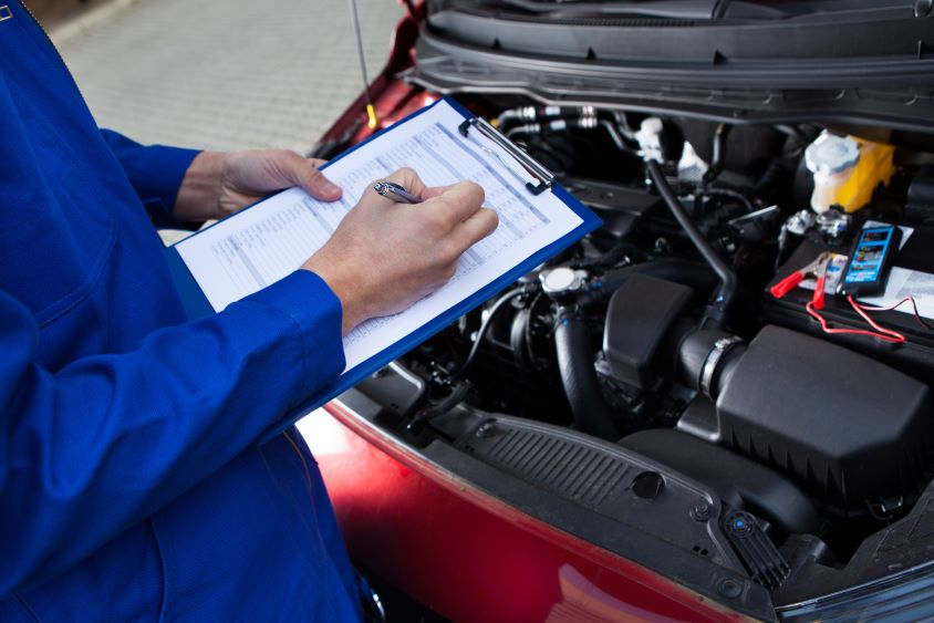 Mechanic with clipboard inspecting a vehicle's engine