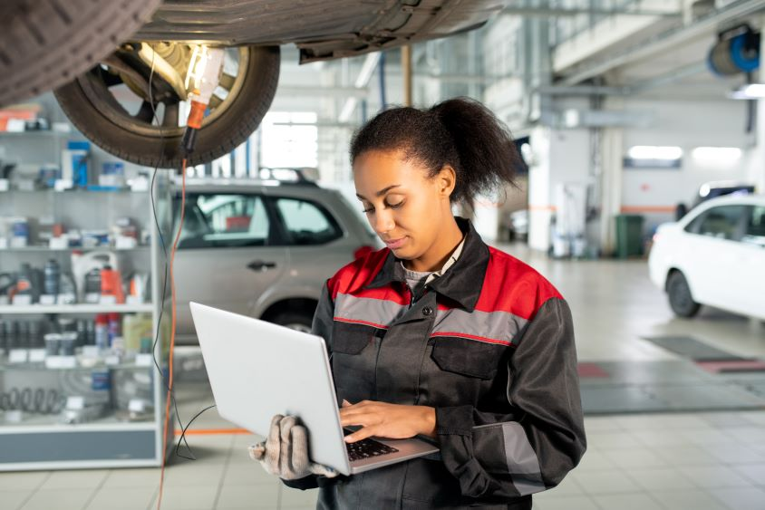 Young female mechanic holding laptop beneath a vehicle