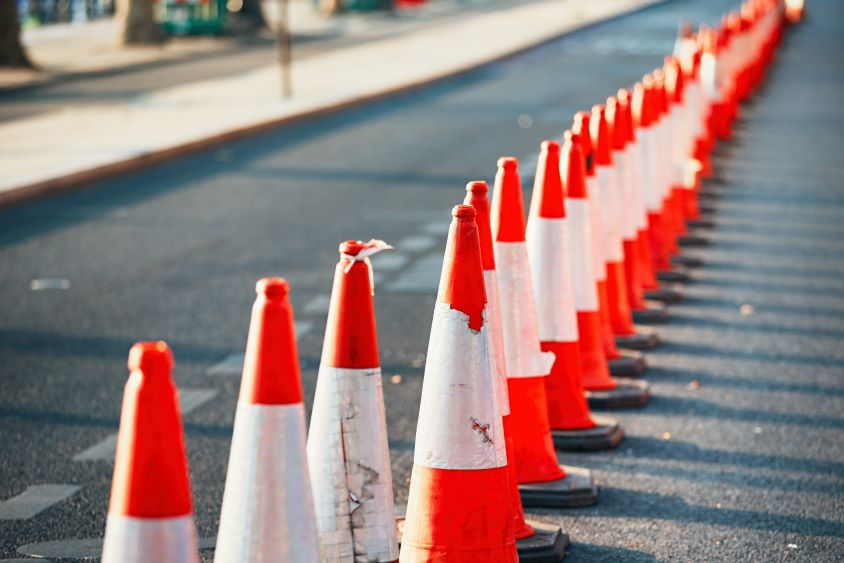 Row of orange traffic cones along the side of a road