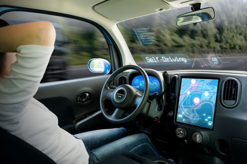 Interior of a self driving car, male driver with his hands behind his head