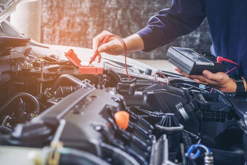 Mechanic using orange equipment to service a car battery