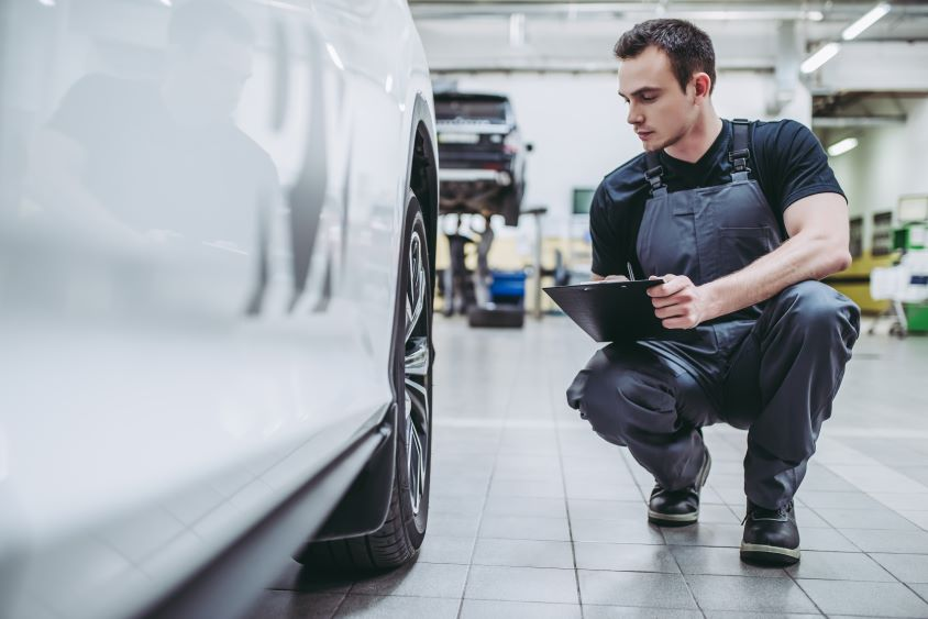 Mechanic in overalls kneeling next to white car in garage, carrying out maintenance checks