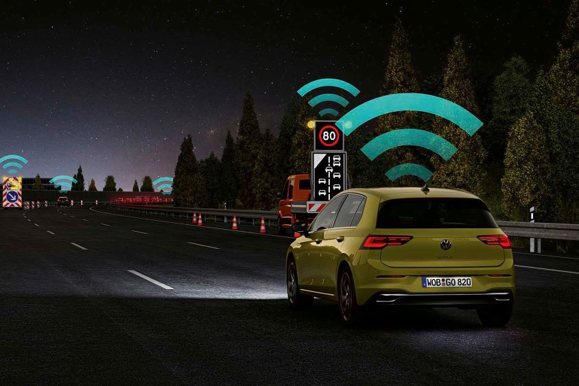 Car driving at night with wifi graphics indicating connectivity