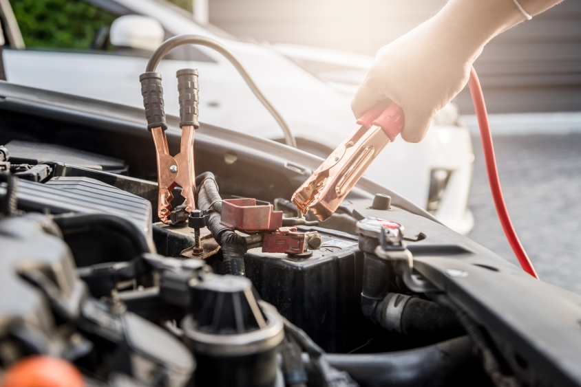 Hand attaching red jump cable to a car engine