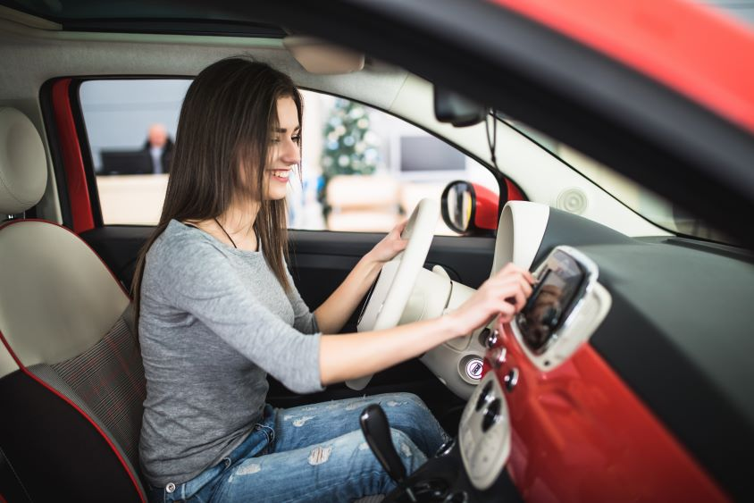 Smiling woman adjusting her car radio in red interior