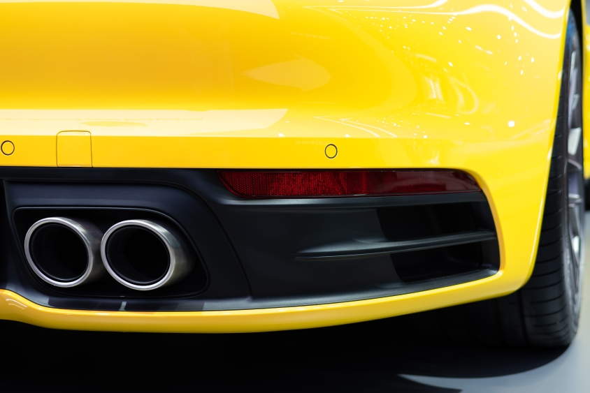 Duel exhaust pipes on the back of a yellow sports car
