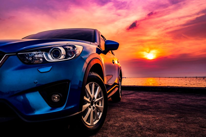 Car parked on beach with sunset in background