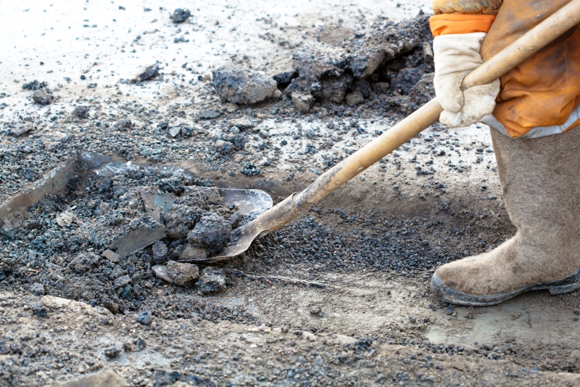 Worker in hi-vis apparel using a spade during road maintenance
