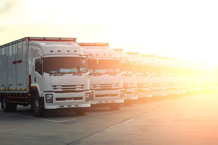 Row of HGVs with trailers with intense sunlight