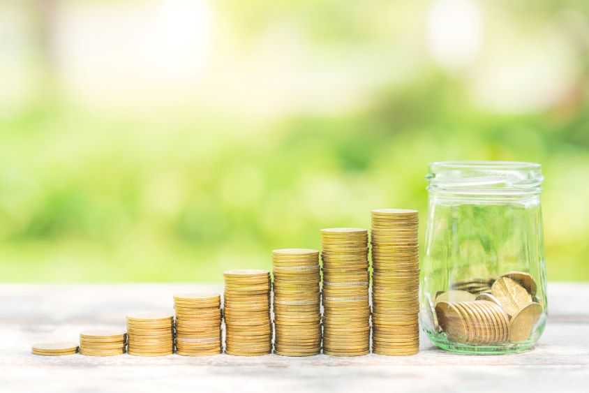 A row of gold coins stacked next to a half full jar of coins with green background