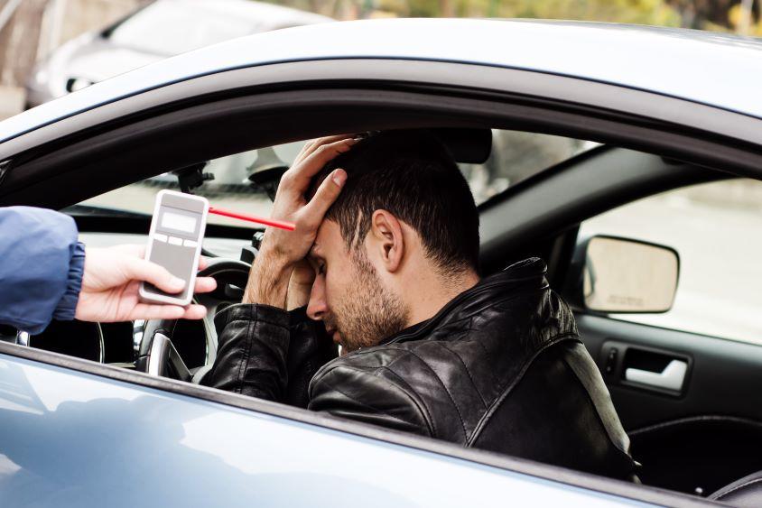 Distressed man in car being encouraged to take a breathalyzer test
