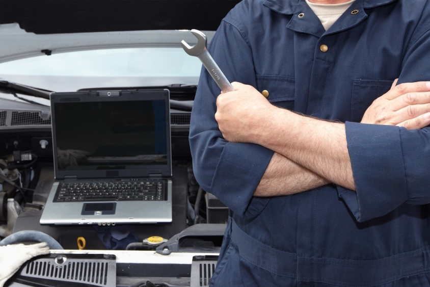 Mechanic with arms crossed holding spanner next to a car engine and a laptop