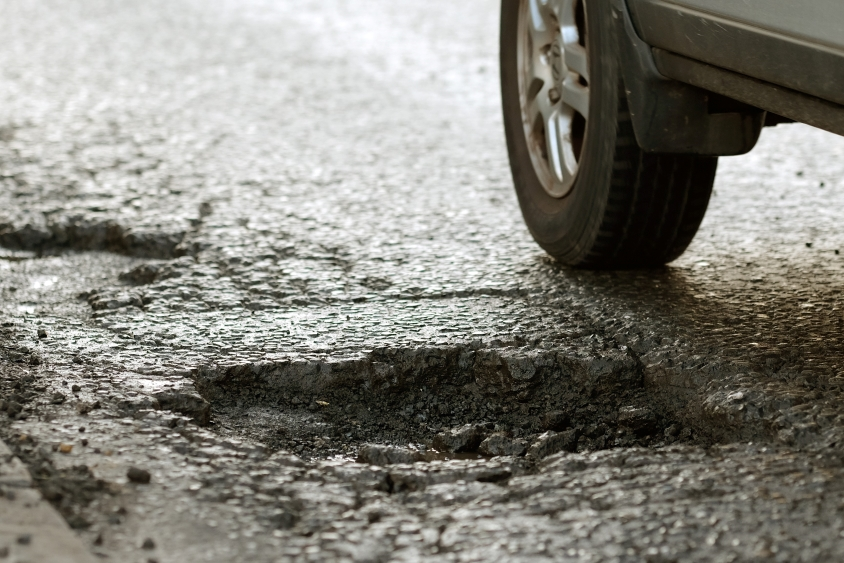 Tire of a car narrowly missing a pothole on road