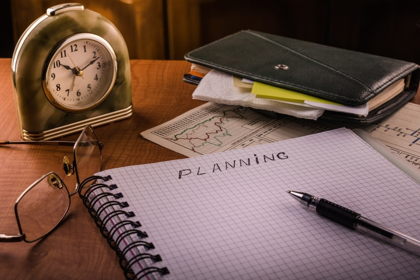 """Notebook on desk on a page that reads """"planning"""" with pen"""