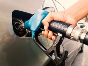 A hand holding a petrol pump refuelling a car