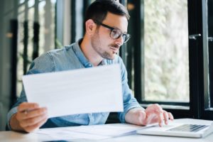 Man at a laptop simultaneously looking at documents