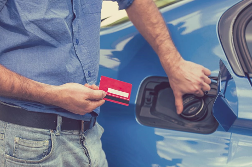 Man opening fuel tank of car while holding a card for payment