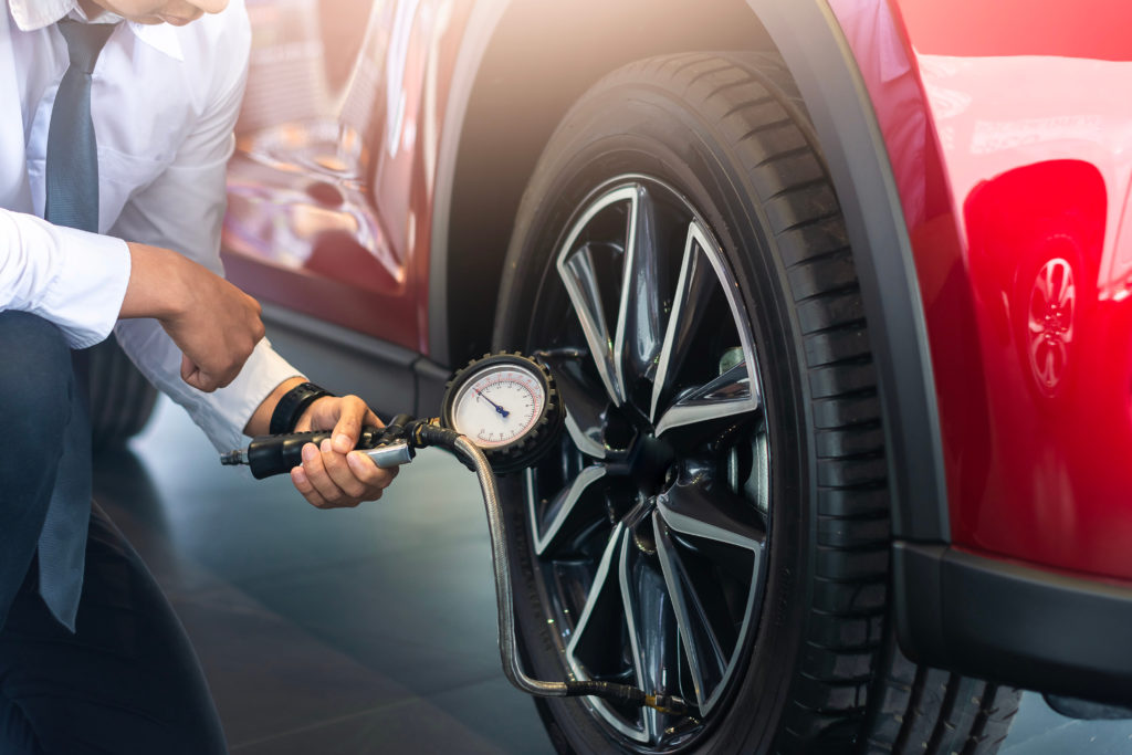 Image of a man kneeling to check the pressure of his vehicle's tyres