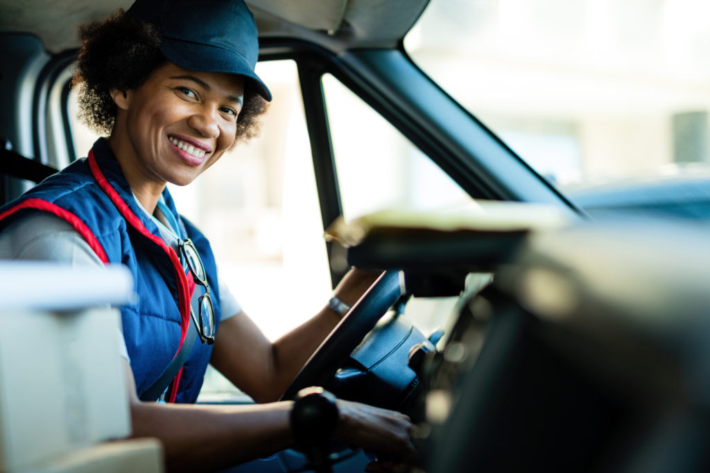 Image of a female courier in the driver's seat of a vehicle