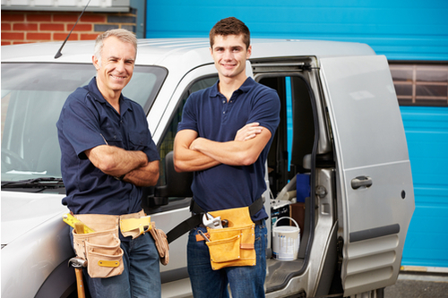Two work men standing next to a van filled with tools