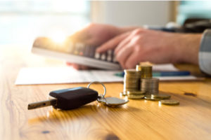 Image of car keys and money on a table with a man using a calculator