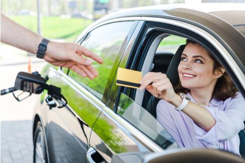 Woman sat in car using fuel card