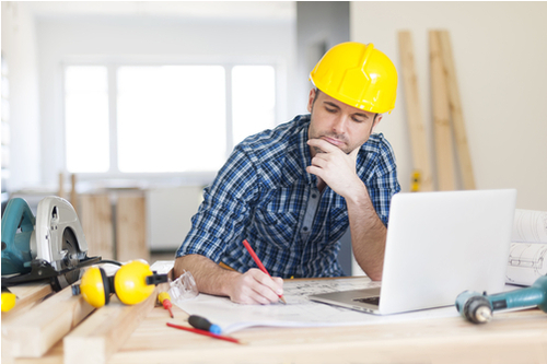 Construction worker sat at computer