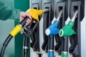 Close-up photo of a man lifting a fuel nozzle from a pump.