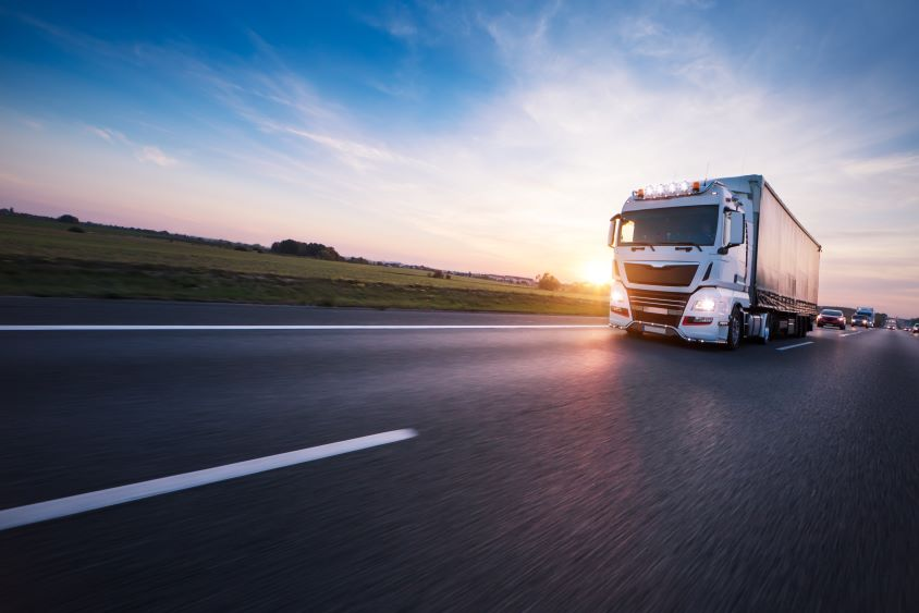 Lorry driving along European highway at sunset