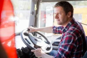 Truck driver driving in cab of semi-truck