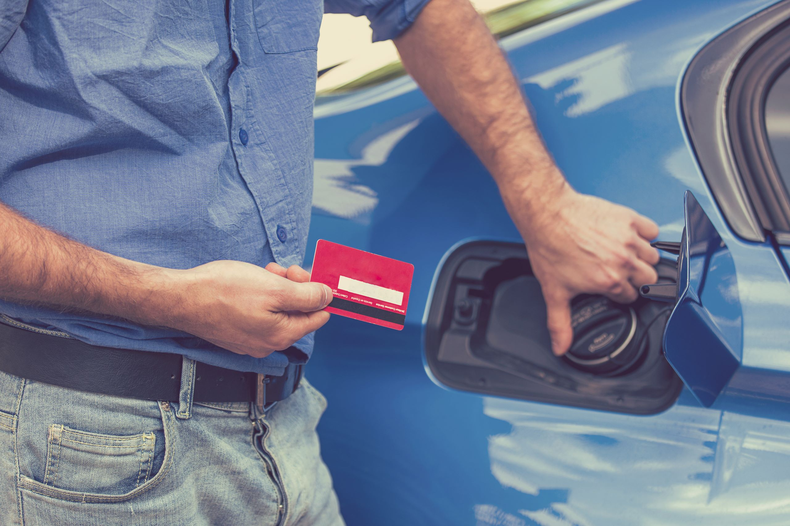 Man with fuel card opening fuel tank of his car