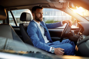 Man in suit behind the wheel of a car