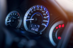 Closeup of car dashboard showing dials and odometer.