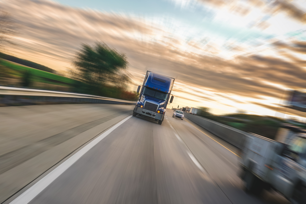 Big 18 wheeler semi truck on highway with motion blur