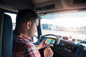 Truck driver in cab using satnav device to plan route