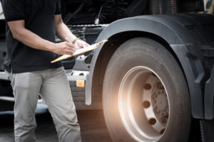 Truck driver holding clipboard daily checking safety truck wheels, vehicle maintenance checklist program.