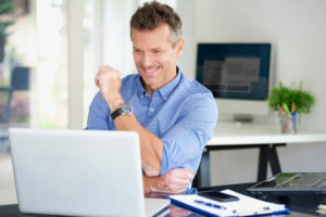 Middle aged businessman wearing shirt while sitting at office desk and using his computer.