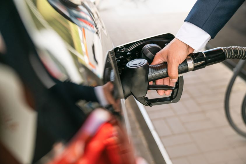Man's hand inserting fuel nozzle into black car